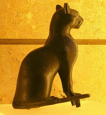 A Black Egyptian statue against a yellow background.