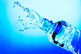 Water is seen splashing from a plastic water bottle against a sky blue background.