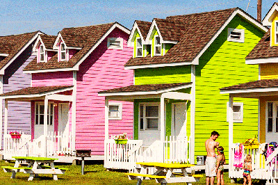 A pair of tiny houses are close together. One is painted bright pink and the other a bright lime green.